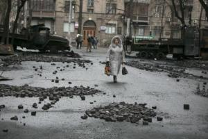 A woman walks past burnt trucks near parliament house in Kiev