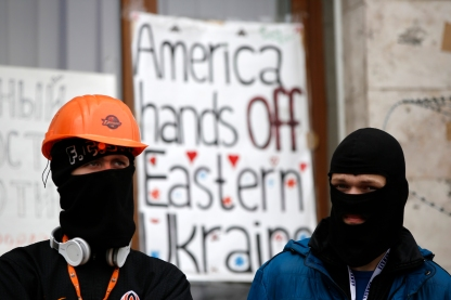 Masked pro-Russian protesters stand guard outside a regional government building in Donetsk