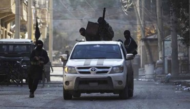 Members of the Islamist Syrian rebel group Jabhat al-Nusra ride on a vehicle mounted with an anti-aircraft weapon, along a damaged street in Deir al-Zor