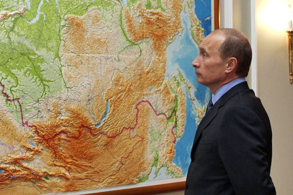 Russian President Vladimir Putin stands in front of the map of Russia and Commonwealth of Independent States between working meetings at his residence Novo-Ogaryovo just outside Moscow, August 11, 2006. REUTERS/ITAR-TASS/PRESIDENTIAL PRESS SERVICE (RUSSIA) - RTR1GAL3